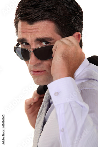 Businessman peering over his sunglasses