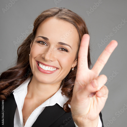 Businesswoman showing two fingers or victory gesture