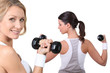 Two women lifting weights together
