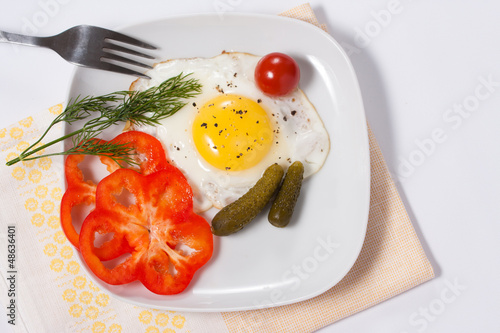Fried eggs with vegetables and greens