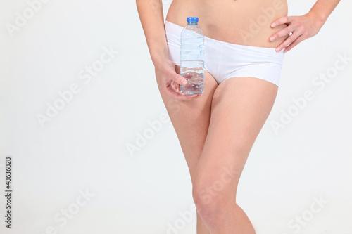 Woman in underwear holding water bottle