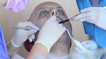 male patient treated with ultraviolet light by his dentist
