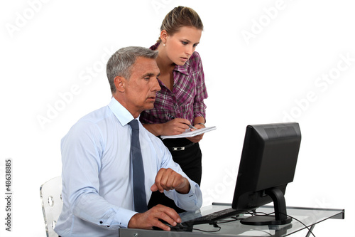 businessman in office with computer and young female assistant