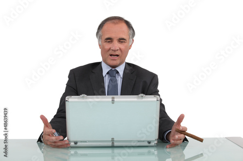 Senior businessman sat with cigar and metal briefcase