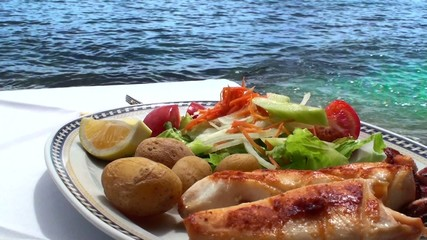 Seafood salad with squid and fresh vegetable on sea background