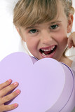 Little girl holding heart-shaped box