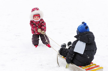 Cute kindergarten girl pulling her young brother on sled