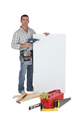 Carpenter using drill to point to poster