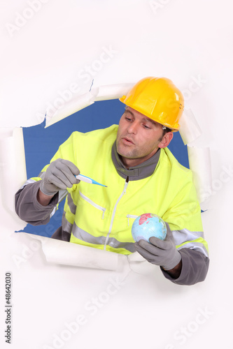 Builder holding globe and pregnancy test