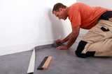 Man putting down linoleum on a baseboard