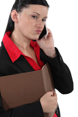 Doubtful businesswoman talking on her mobile phone