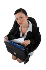 Businesswoman getting documents out of a briefcase