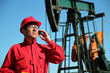 Oil Worker Using Cell Phone Next to Pumpjack