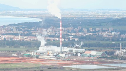 chimney of an industrial plant  as viewed from Scarlino, Italy