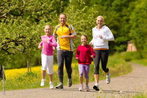 Family running in the meadow for sport