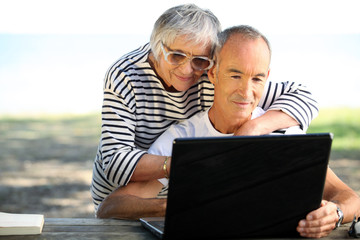 65 years old couple doing computer outside
