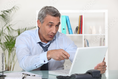 Businessman laughing in front of a laptop