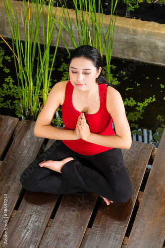 Asian woman doing yoga in tropical setting