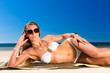 Attractive woman lying in the sun on beach