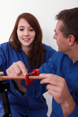 Plumber instructing young female trainee