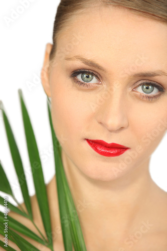 Blond woman holding green plant leaf