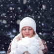 happy woman with closed eyes holding snow