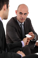 Two businessmen exchanging cards