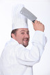 Chef in uniform wielding a cleaver