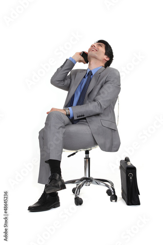 Man sitting in a chair by phone