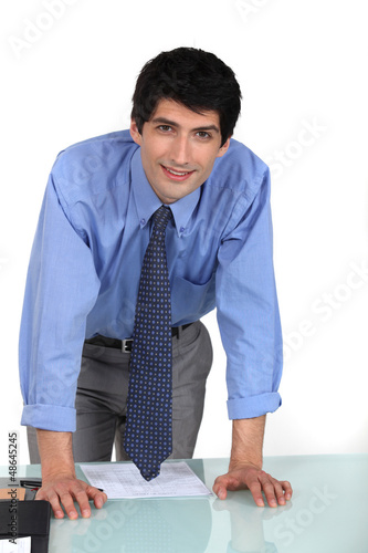 Young office worker leaning on his desk
