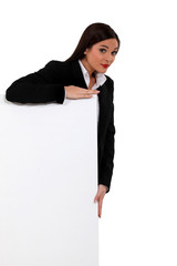 Businesswoman standing behind a white sign