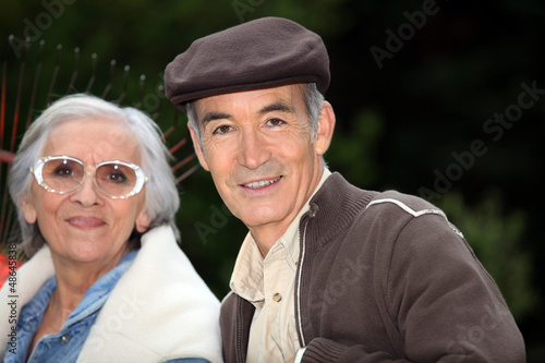 Elderly couple with garden rake