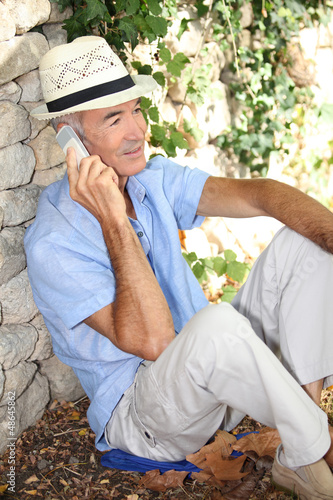 Old man sat by stone wall whilst on vacation
