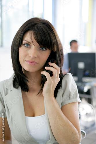 Secretary stood in open-plan office