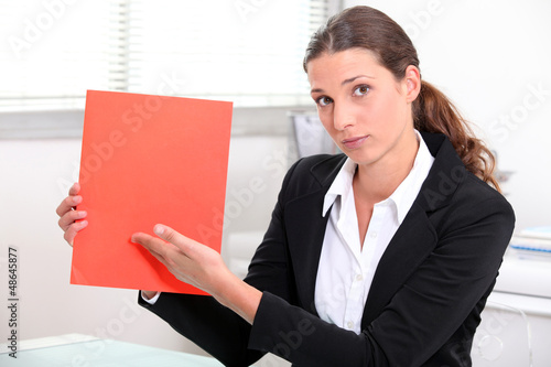Woman at desk showing document