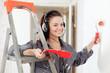 woman in headphones paints wall