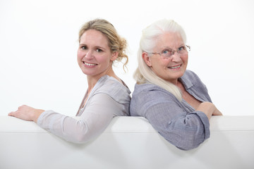 Mother and daughter sitting on white sofa