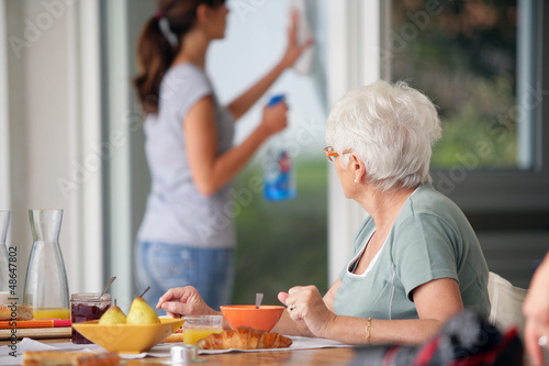 senior woman having breakfast with home care in the background