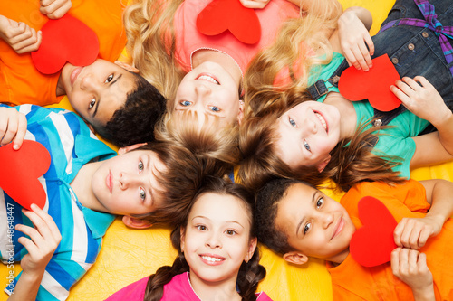 Kids laying in circle with hearts in their hands
