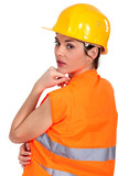Tradeswoman wearing a hart hat and an orange vest