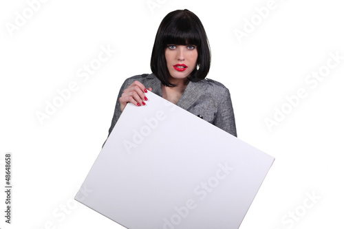 Brunette businesswoman holding a poster