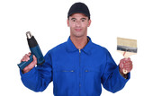 Tradesman holding a paintbrush and a screw gun