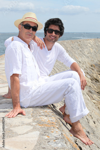 Grownup father and son sitting on a harbor wall