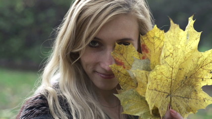 Happy woman with golden maple leafs, slow motion