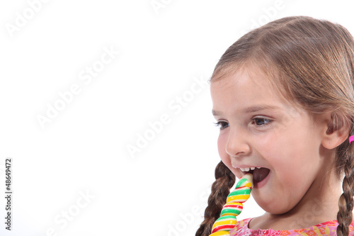 little girl eating a candy, looked amused and impish
