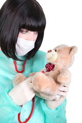 nurse examining a teddy bear with a stethoscope