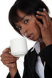 Businesswoman drinking coffee during call