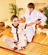 Male masseur doing massage woman in bamboo spa.