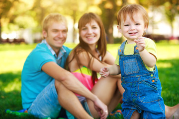 smiling baby with parents in a beautiful summer park