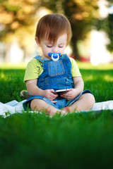 baby is playing with phone on the green grass